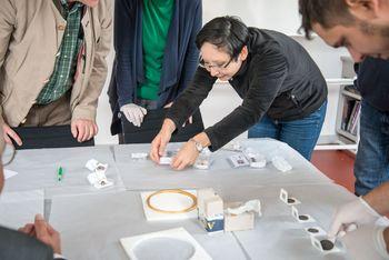 Vorsichtig nimmt Tomoko Emmerling einen in Seidenpapier eingeschlagenen Fund zur Begutachtung in die Hand. © Landesamt für Denkmalpflege und Archäologie Sachsen-Anhalt.