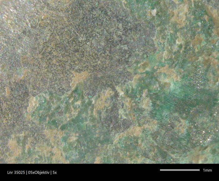 Das sieht die Restauratorin durch das Binokular: Die Malachitschichten (grün) und Sedimentreste (gelbbraun) liegen über der Originaloberfläche und sollen abgenommen werden. © Archäologischer Dienst des Kantons Bern, Sabine Brechbühl.