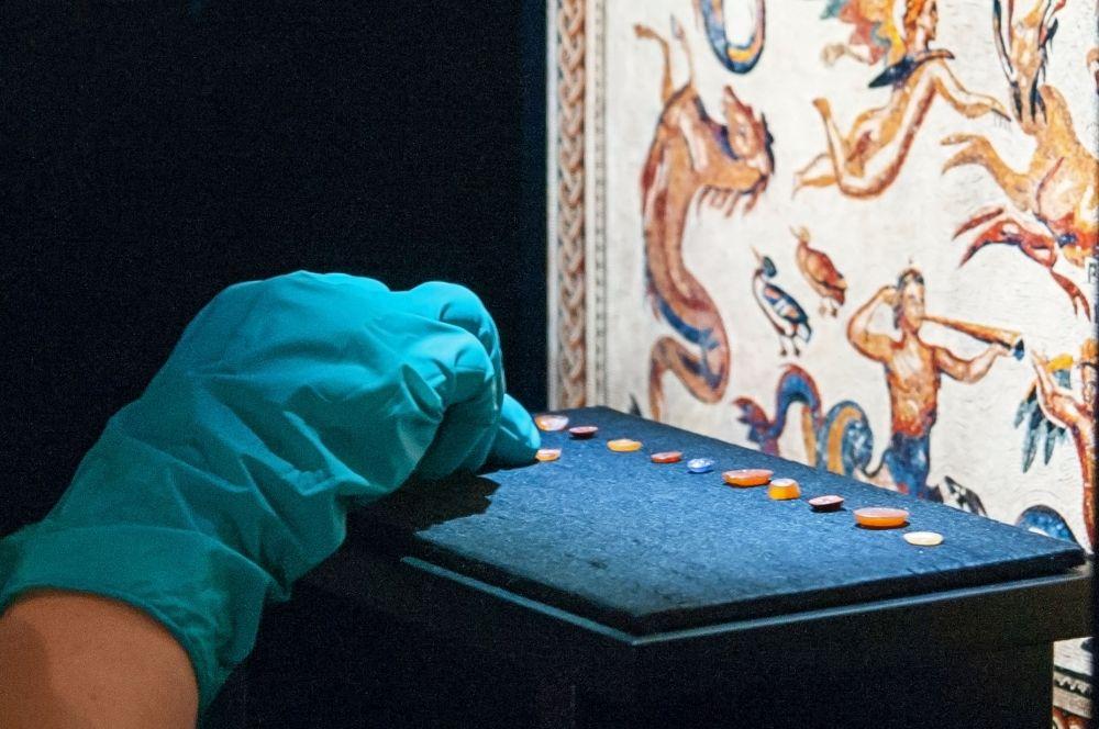 Mit großem Fingerspitzengefühl und ganz vorsichtig positioniert eine Mitarbeiterin der Firma Fißler und Kollegen die römischen Gemmen aus dem National Museum Wales in Cardiff an ihren Plätzen. © Landesamt für Denkmalpflege und Archäologie Sachsen-Anhalt.