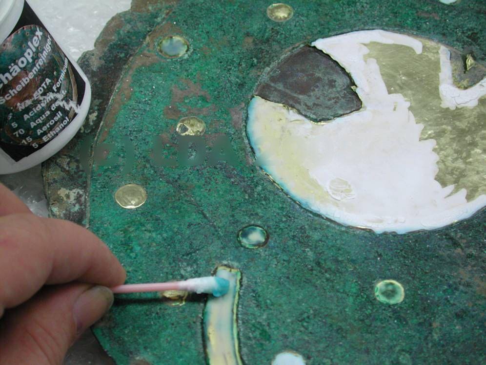 Archäoplex ist eine Komplexierungspaste, bestehend aus chemischen Reagenzien, die mit einem Kieselgel zu einer Paste angedickt wurden. Mit diesem Material konnten die Korrosionsauflagerungen auf den Goldblechen gezielt angelöst werden, ohne die Malachitpatina der Bronzeoberfläche anzugreifen. © Landesamt für Denkmalpflege und Archäologie Sachsen-Anhalt.