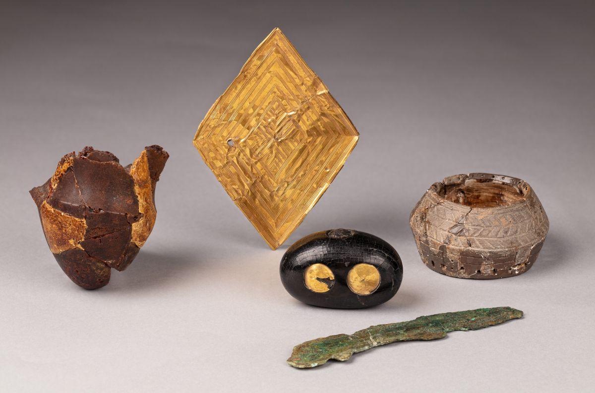 Die sogenannte Clandon-Barrow-Raute aus Gold mit weiteren Beifunden. Diese stammen alle aus dem gleichnamigen Hügelgrab aus der Nähe von Dorchester, Großbritannien. Ein ähnliches Stück stammt aus dem Grabhügel ›Bush Barrow‹ bei Stonehenge. © Dorset County Museum.